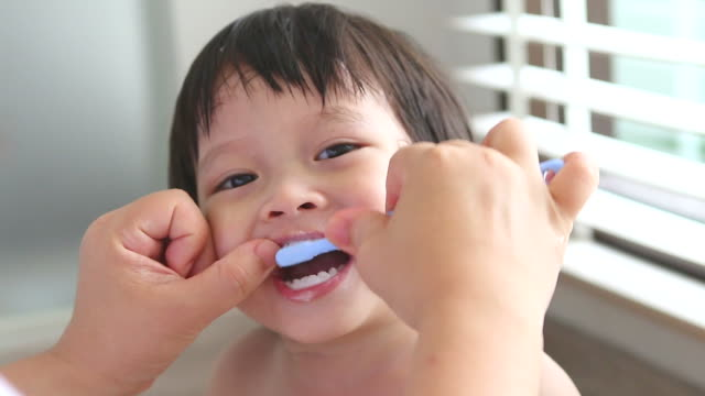 hd:mom is helping son brush his teeth - human teeth stock videos & royalty-free footage