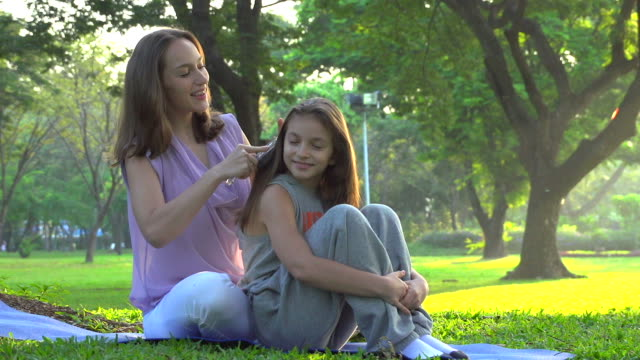 stockvideo's en b-roll-footage met hd:mother is combing the daughter's hair at the park. - kammen