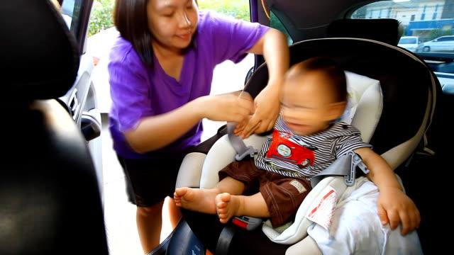 vídeos y material grabado en eventos de stock de hd: madre cuidar de su bebé en el cinturón de seguridad. - presidente de organización