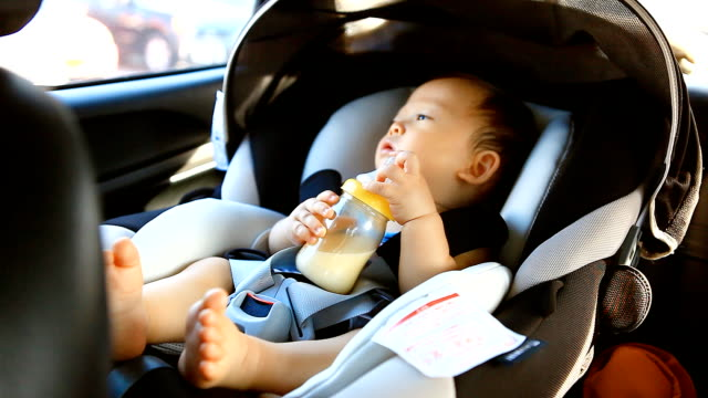 vídeos y material grabado en eventos de stock de hd: portrait of a little boy beber leche en el coche. - cochecito de bebé