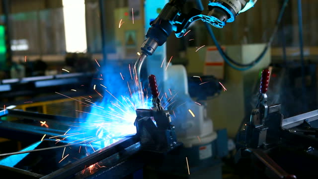 HD:Robotic arm welding in factory.