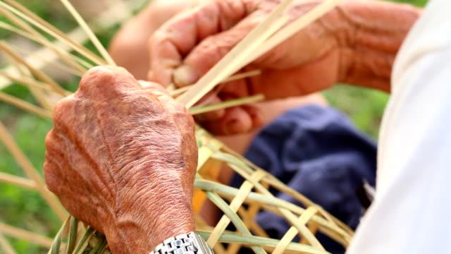 HD:Senior hands manually weaving bamboo basket.