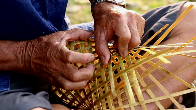 HD:Senior hands manually weaving bamboo basket.