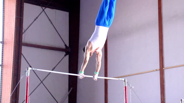hd:shot of male gymnast performing routine on horizontal bar - horizontal bar stock videos and b-roll footage
