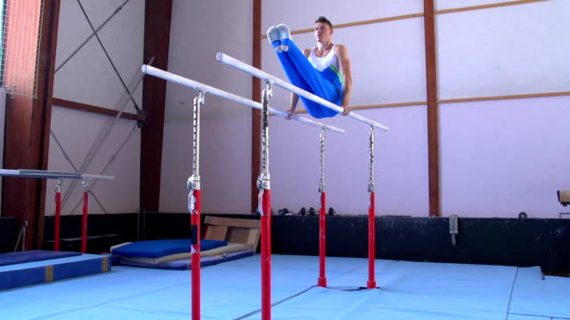 stockvideo's en b-roll-footage met hd:shot of male gymnast performing routine on parallel bars - de brug