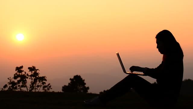 vídeos de stock, filmes e b-roll de hd: silhueta de mulher digitando no laptop horário do pôr do sol - deus