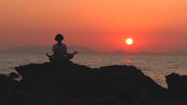 vídeos y material grabado en eventos de stock de hd: silueta de mujer joven de loto yoga meditación. - posa del loto