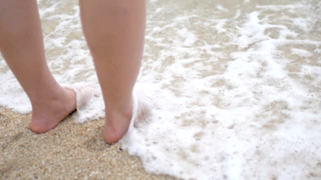 HD:Slow motion of foot on the beach with sea wave