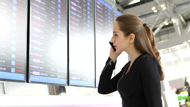 HD:Smiling businesswoman discuss about schedule display at the airport.