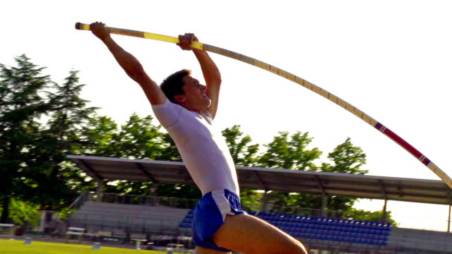 hd: super slo-mo schuss von junger sportler performing at pole vault - stange stock-videos und b-roll-filmmaterial