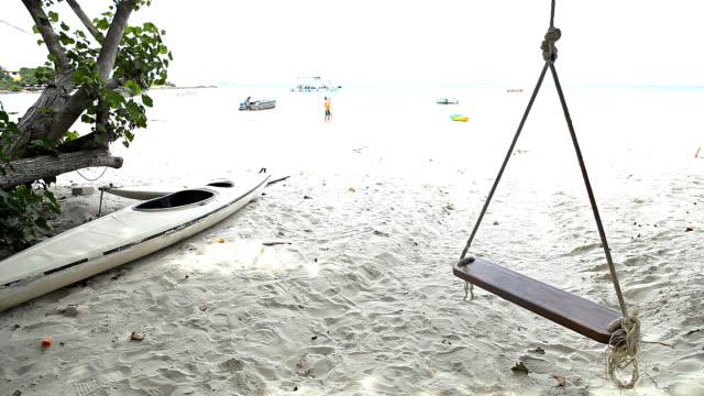 hd:swing and a boat on the beach. - tropiskt träd bildbanksvideor och videomaterial från bakom kulisserna