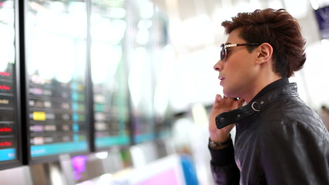 HD:Traveller checking flight schedule at the airport.