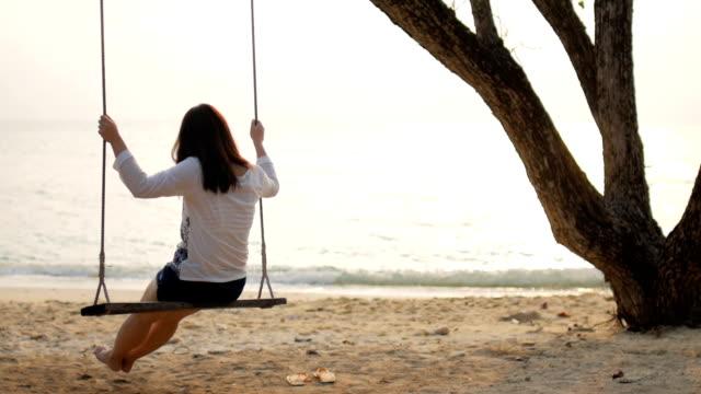 hd :  frau auf schaukel am strand mit meerblick ein sonnenuntergang zeit, zeitlupe, entspannung konzept - wippe stock-videos und b-roll-filmmaterial