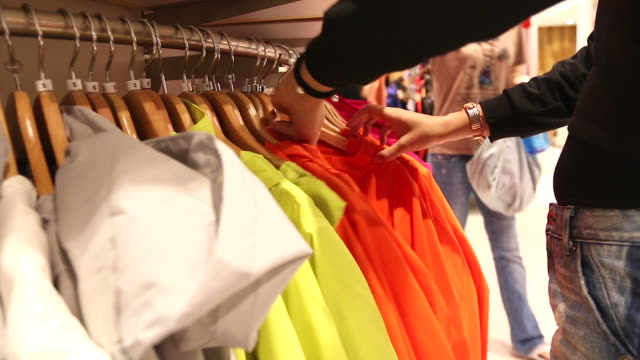 HD:Woman selecting items in a clothes shop.