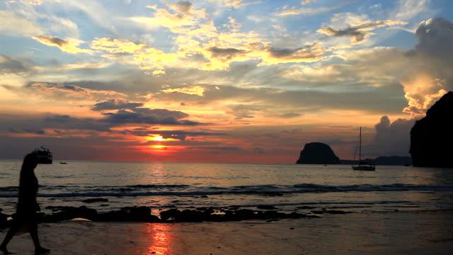 HD: Donna cammina sulla spiaggia al tramonto