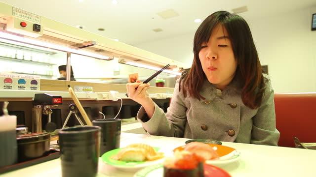HD:Young beautiful asian woman eating sushi with chopsticks