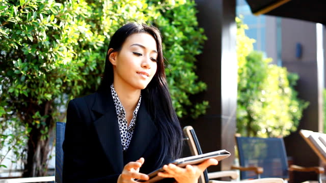 HD:Young business woman working with tablet.