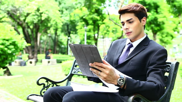 HD:Young businessman working by using tablet in the park..