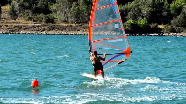 HD:Young male windsurfer at slalom regatta