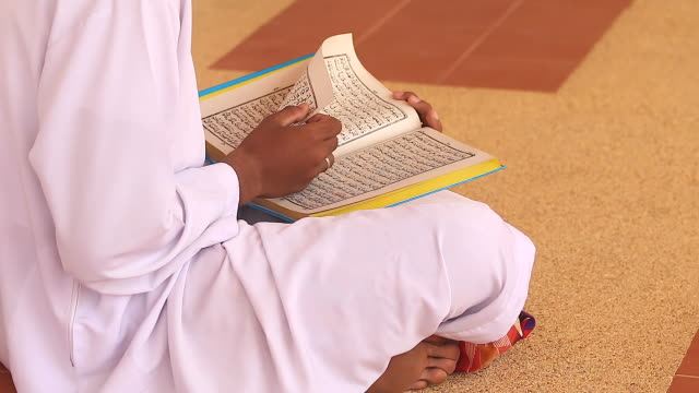 hd:young man reading the koran at the mosque. - koran stock videos and b-roll footage