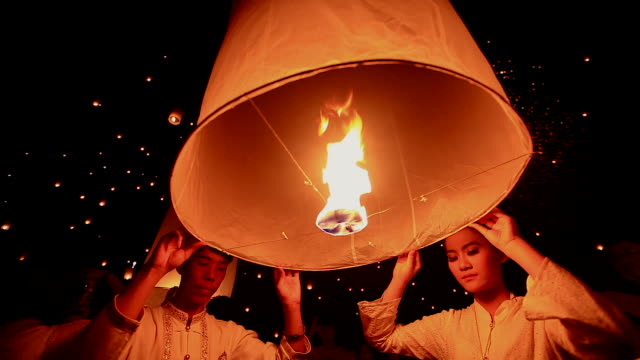 HD:Young people release floating lanterns to the sky.