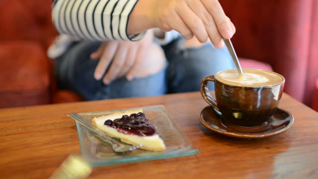 HD:Young woman drink coffee and cake blueberry pie in coffee house
