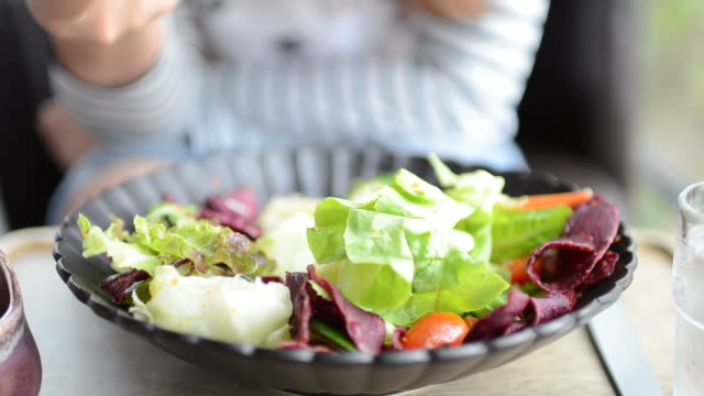 vídeos y material grabado en eventos de stock de hd: joven mujer comiendo una ensalada con crema souce - antioxidante
