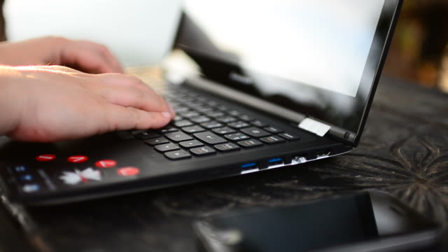 HD:Young woman typing on laptop keyboard
