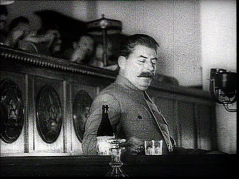 he drinks a glass of water while audience claps and then speaks kalinin sitting at the presidium mcu kaganovich standing w/ headphones in one hand - ex unione sovietica video stock e b–roll