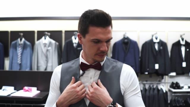 vidéos et rushes de il est de choisir la bonne combinaison pour son mariage dans une élégante boutique tendance - smoking