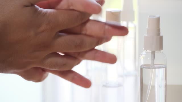 vidéos et rushes de il se nettoie les mains avec du spray à l'alcool. - hot desking