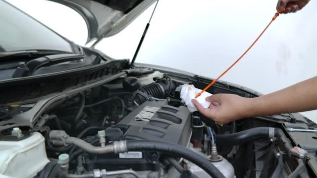 vídeos de stock, filmes e b-roll de ele está a manutenção de seu próprio carro pessoal por si mesmo. - motor