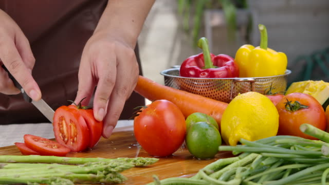 he is using a knife to cut tomatoes. - farm to table stock videos & royalty-free footage