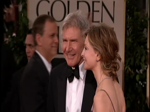he is wearing a black tux with a bow tie and she is wearing a spaghetti strap black gown and her hair is up - calista flockhart stock-videos und b-roll-filmmaterial