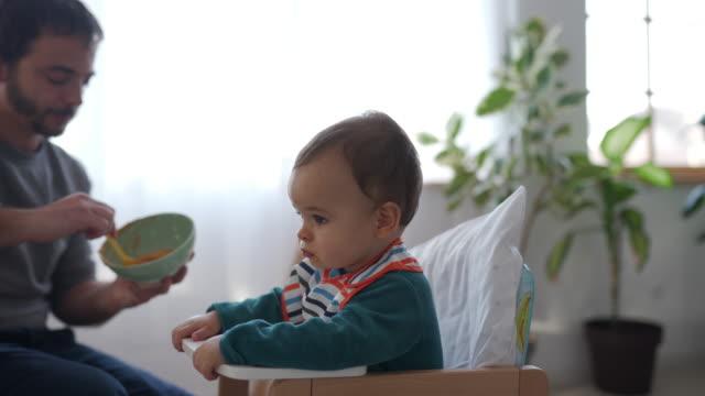 vidéos et rushes de il aime quand le père le nourrit - chambre de bébé