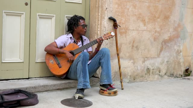 he plays an acoustic guitar and whistle after economic changes there is much more flexibility for those who want to make a living out of... - gitarre stock-videos und b-roll-filmmaterial