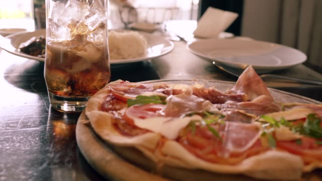 he was picking pizza parma ham from the wooden pan and a glass of cola on the side. - refreshment stock videos & royalty-free footage