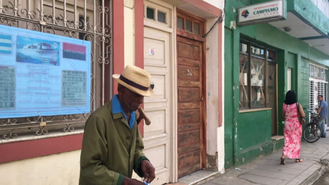 vidéos et rushes de he wears traditional clothing of the cuban past in the back there is a mural full of symbols and news regarding the cuban revolution the image... - révolution cubaine