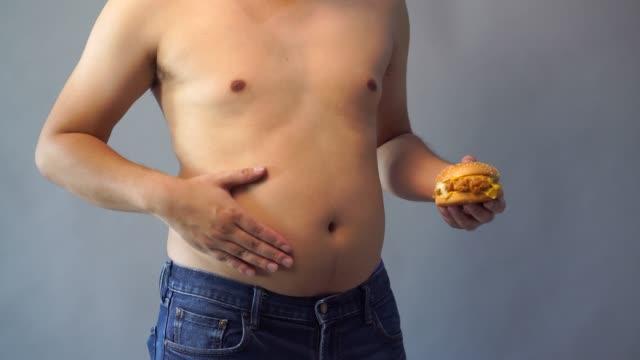 彼はハンバーガーを持っている手の肥満を心配しました。 - unhealthy eating点の映像素材/bロール