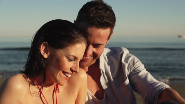 head and shoulders dolly shot of young couple sitting on beach. - 2人点の映像素材/bロール