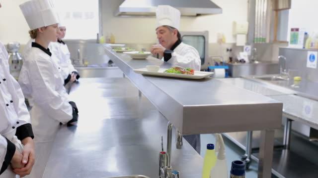 vidéos et rushes de head chef correcting the meals in the kitchen - apprenti