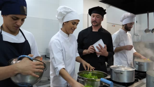 head chef giving instructions to a female sous chef about a salad she is making both smiling - cucina commerciale video stock e b–roll