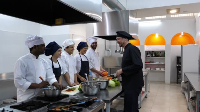head chef giving instructions to his team of everything they are going to prepare all looking very happy - learning stock videos & royalty-free footage