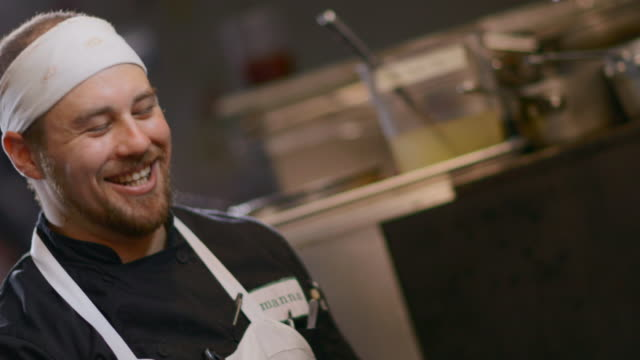 Head chef laughs with staff in restaurant kitchen