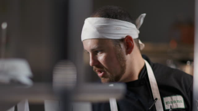 vídeos de stock, filmes e b-roll de head chef reads meal orders out loud and directs kitchen staff in restaurant kitchen - autoridade