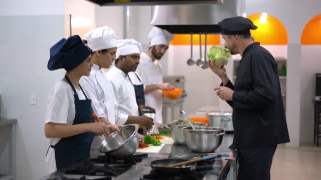 head chef teaching his students about a healthy lettuce smelling it and letting other students smell while they are concentrating on other tasks - insegnante video stock e b–roll