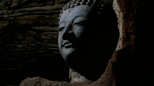 Head of Buddha in underground cave, dolly shot.