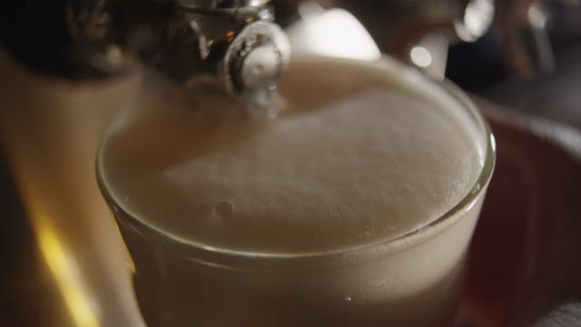 head on pint of beer overflows - beer glass stock videos & royalty-free footage