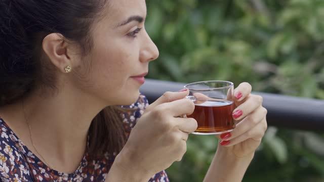 vídeos de stock, filmes e b-roll de tiro na cabeça close-up de mulher jovem hispânica bebendo uma xícara de chá quente no terraço ao ar livre - atividade recreativa