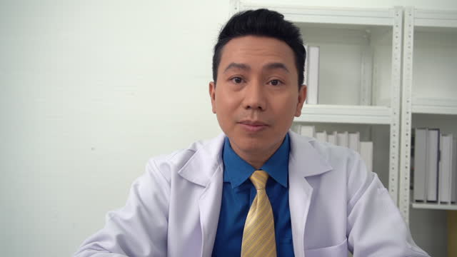 head shot of male medical assistant wears white coat video calling distant patient - general practitioner stock videos & royalty-free footage
